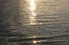 Weerspiegelingen van zonlicht op water bij zonsondergang royalty-vrije stock foto