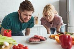 weerzinwekkend veganistpaar die ruw vlees op plaat in keuken bekijken royalty-vrije stock foto's