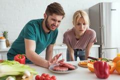 weerzinwekkend veganistpaar die ruw vlees op plaat in keuken bekijken royalty-vrije stock afbeelding