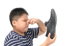 Weerzinwekkende jongen die een paar stinkende leerschoenen houden stock foto