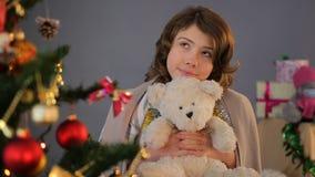 Weesmeisje die zich dichtbij Kerstboom bevinden en een wens, kinderjaren, vakantie maken stock footage