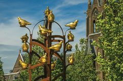 Golden metal birds monument with leafy tree and steeple in sunny day at Weesp. Weesp, northern Netherlands - June 23, 2017. Golden metal birds monument with stock image