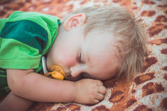 Weet blond little boy asleep on a blanket Royalty Free Stock Image