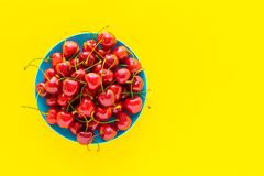 Weet cherry in a blue plate on a yellow background. Stock Photos