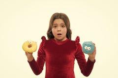 Weet geen welke om eerste Klein jong geitje in doughnutbakkerij te eten Weinig kind met grappige donuts Aanbiddelijk klein meisje stock foto's