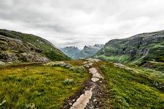 Weg über grüner Weide in den Bergen von West-Norwegen mit Schnee auf den Gipfeln und einem dunklen bewölkten Himmel Lizenzfreies Stockfoto