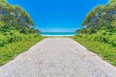 Weg aan paradijs, aphalt staaf die op tropisch strand met turkoois zeewater beëindigen stock afbeelding