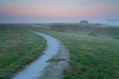Weg auf Ackerland während des nebelhaften Sonnenaufgangs Lizenzfreie Stockfotos
