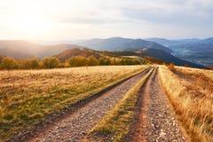 Weg in de bergen Het prachtige landschap van de de herfstberg majestueuze, donkere wolken in zonlicht net bos  Royalty-vrije Stock Afbeelding