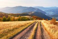 Weg in de bergen Het prachtige landschap van de de herfstberg majestueuze, donkere wolken in zonlicht net bos  Royalty-vrije Stock Fotografie