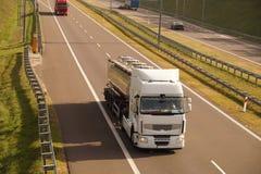 Weg in de de herfstzon De vrachtwagens en de auto's bewegen zich bij hoge snelheid stock afbeelding