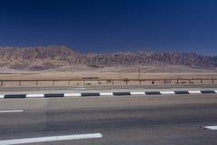 Weg in de woestijn in Israil in zonnige dag met mening aan rode iordan bergen en blauwe hemel stock foto