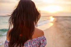 Weg der jungen Frau auf einem leeren wilden Strand in Richtung zu den himmlischen Lichtstrahlen fallend vom Himmel, Stockfotografie