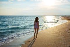 Weg der jungen Frau auf einem leeren wilden Strand in Richtung zu den himmlischen Lichtstrahlen fallend vom Himmel, Stockfotos