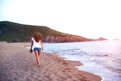 Weg der jungen Frau auf einem leeren wilden Strand in Richtung zu den himmlischen Lichtstrahlen fallend vom Himmel Stockfoto