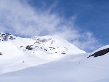Weg die de sneeuwberg met donkere weerhemel kruisen Royalty-vrije Stock Foto's