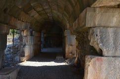 Weg door een donkere gebogen overspannen tunnel in oude steenruïnes stock fotografie