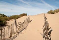 Weg door een gebroken omheining op zandig strand Royalty-vrije Stock Afbeeldingen