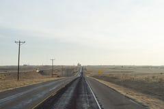 Weg door woestijnlandschap bij de ochtend van een zonnige dag. Stock Foto's