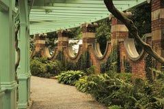 Weg durch Pergola in ummauertem Garten stockfoto