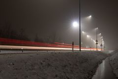 Weg in een lichte mist die door lantaarns wordt verlicht De route is voorgenomen voor de beweging van passagiersvoertuigen en vra royalty-vrije stock afbeelding