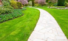 Weg in een tuin met weelderig groen gazon Stock Fotografie