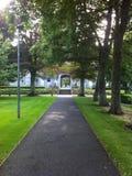 Weg in einem Grün, das zu einen Eingang führt Lizenzfreies Stockfoto
