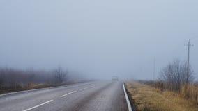 Weg en een auto in mist Royalty-vrije Stock Foto