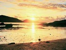 Weg innerhalb des Sonnenuntergangs auf Strand Spiegelung des sunsetting Horizontes im Meerwasser zwischen Felsen stockfotografie