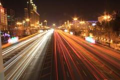 Weg met autoverkeer bij nacht met onscherpe lichten Stock Foto's