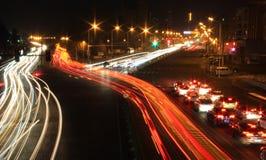 Weg met autoverkeer bij nacht met onscherpe lichten Stock Fotografie