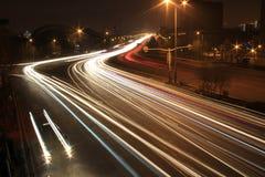 Weg met autoverkeer bij nacht met onscherpe lichten Royalty-vrije Stock Afbeeldingen