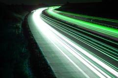 Weg met autoverkeer bij nacht met onscherpe lichten stock foto