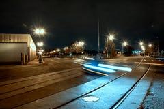 Weg met het bewegen van auto en treinsporen bij nacht stock afbeeldingen
