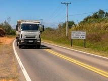Weg met nieuwe verkeersteken die de nieuwe wet informeren die in de loop van de dag het gebruik van koplampen op zelfs op de wege royalty-vrije stock foto