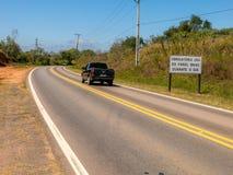 Weg met nieuwe verkeersteken die de nieuwe wet informeren die in de loop van de dag het gebruik van koplampen op zelfs op de wege royalty-vrije stock fotografie