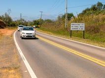 Weg met nieuwe verkeersteken die de nieuwe wet informeren die in de loop van de dag het gebruik van koplampen op zelfs op de wege Stock Fotografie
