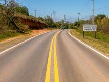 Weg met nieuwe verkeersteken die de nieuwe wet informeren die in de loop van de dag het gebruik van koplampen op zelfs op de wege Royalty-vrije Stock Afbeelding