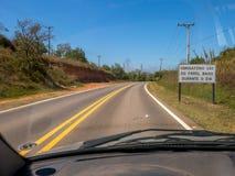 Weg met nieuwe verkeersteken die de nieuwe wet informeren die in de loop van de dag het gebruik van koplampen op zelfs op wegen g Royalty-vrije Stock Foto's