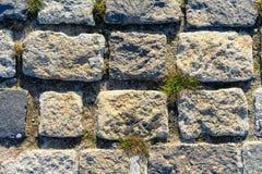 Weg met ruwe ruwe grijze steen als achtergrond of textuur wordt gevoerd die royalty-vrije stock afbeelding