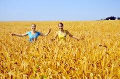 Weg mit zwei Mädchen durch goldenes Feld Stockfotografie