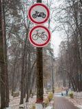 Weg, nat na sneeuwval, in het park met verbodstekens voor motorrijders Stock Afbeeldingen