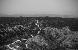 Weg nergens, zwart-wit beeld van weg onder heuvels en stock afbeelding