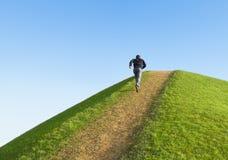 Weg omhoog de heuvel. De mens liep tot de bovenkant. Royalty-vrije Stock Fotografie