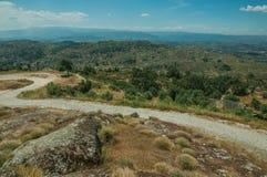 Weg over heuvelig die landschap door rotsen en struiken wordt behandeld stock foto's