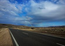 Weg, Steppe und unbegrenzter Himmel mit Regenbogen im Patagonia Argentinien lizenzfreies stockbild