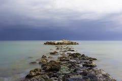 Weg van rotsen op water Stock Foto's
