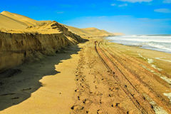 Weg van zand tussen de oceaan en de woestijnduinen royalty-vrije stock foto