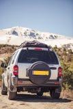 Weg vom Straßenauto in den schneebedeckten Bergkuppen Lizenzfreie Stockfotos