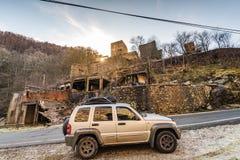 Weg vom Straßenauto durch verlassenes gebranntes Dorf Lizenzfreie Stockbilder